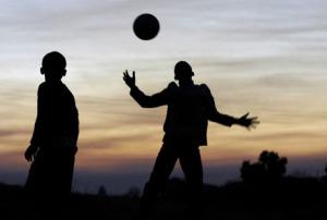 Boys play football at dusk in the township of eThandakukhanya in Mpumalanga.